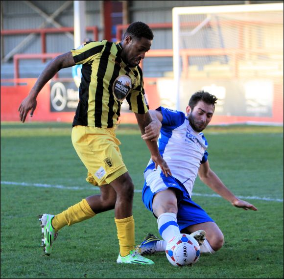 Nathan Modest is loses control to a sliding challenge from a Barrow defender