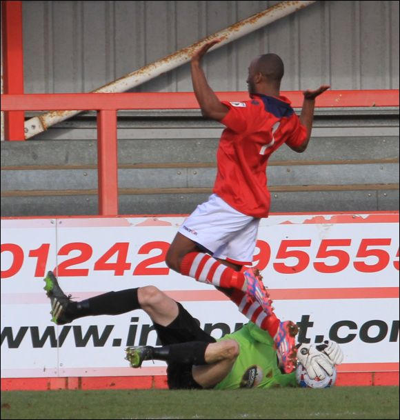 Colwyn Bay's Obi Anouro dances around as headless City keeper Paul White claims the ball