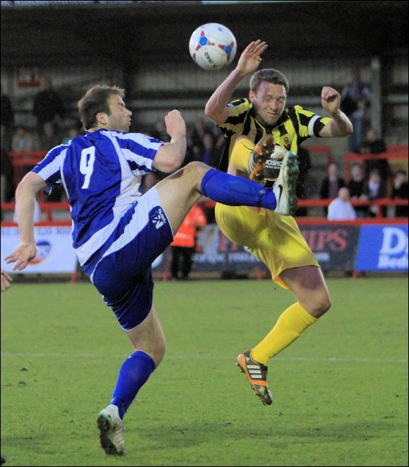 Tom Webb in some high kicking action with ex-City striker Mike Symons at Kidderminster tonight